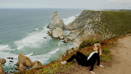 Beautiful woman relaxes at Cabo da Roca in Portugal - Sintra Natural Park - travel photography Stok Fotoğraf