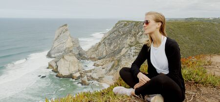 Beautiful woman relaxes at Cabo da Roca in Portugal - Sintra Natural Park 版權商用圖片