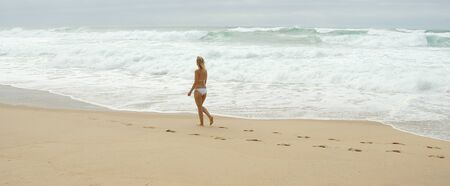 Walk along a sandy beach at the Ocean - Young woman on summer holiday