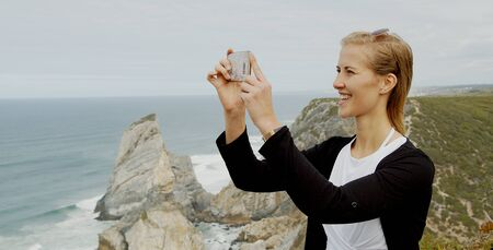 Young woman enjoys the view over the ocean at Cabo da Roca in Portugal