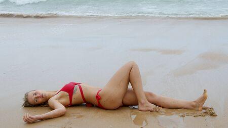 Sexy woman in a bikini relaxes on a sandy beach at the ocean