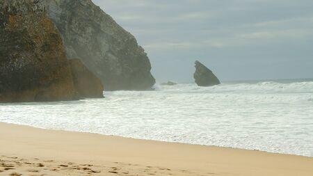 Wild Atlantic ocean coast at Adraga Beach in Portugal