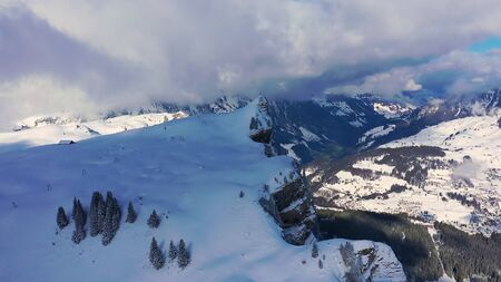 Beautiful sunny winter???′s day in the alps with snow capped mountains - aerial drone footage Stock Photo