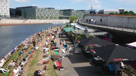 Popular beach club at River Spree in Berlin on a hot summer day - BERLIN, GERMANY - MAY 21, 2018