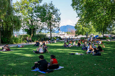 People relax at the lakefront of Lake Lucerne in Switzerland - LUCERNE, SWITZERLAND - AUGUST 16, 2020 Éditoriale