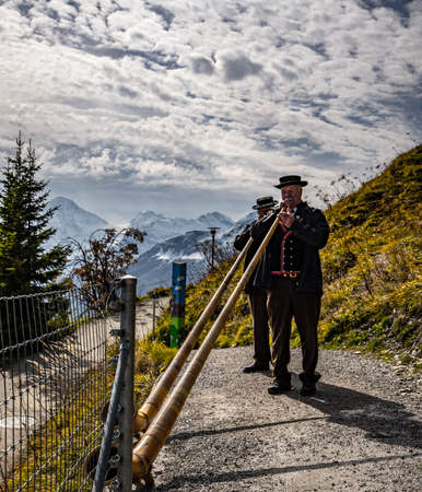 Alphorn musicians in the Swiss Alps - typical view - COUNTY OF BERN. SWITZERLAND - OCTOBER 9, 2020