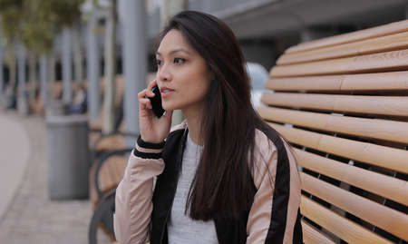 Young Asian woman takes a phone call