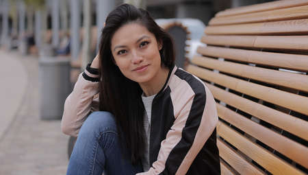 Pretty Asian girl sits on a bench and relaxes