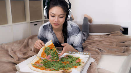 Young woman lying on the bed eats pizza