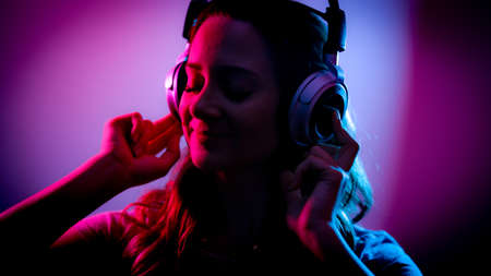 Young woman listens to music on her headphones - stylish illuminated Stok Fotoğraf