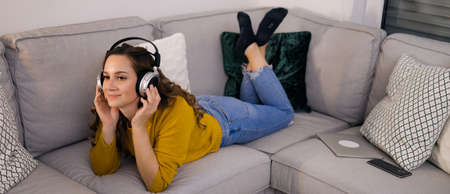Pretty woman listens to music in her apartment and relaxes