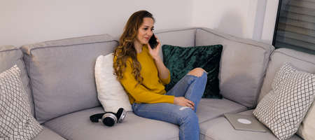Young relaxed woman on the couch on the phone