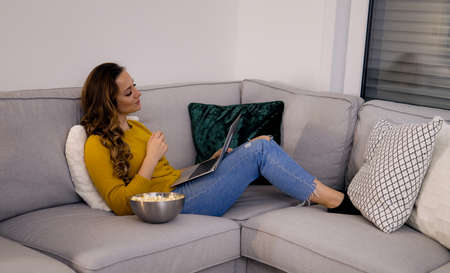 Young woman lies on the couch with her laptop and eats popcorn