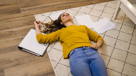 Young woman exhausted from work lying on the floor