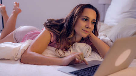 Young woman lies on the bed with her laptop and watches movies Stok Fotoğraf