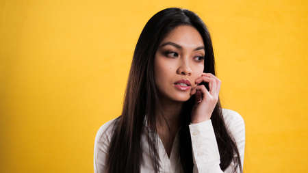 Thoughtful young woman against a yellow background
