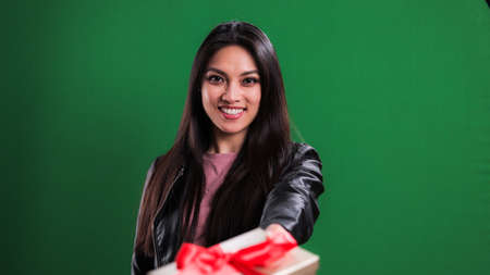 Young woman holds a gift box towards the camera Standard-Bild