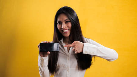 Young pretty woman points to a smartphone Standard-Bild