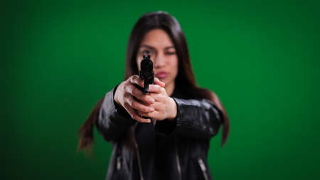 Young female agent with a gun in her hand shoots at the camera