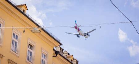 Airplane flies low over the city of Innsbruck - INNSBRUCK, AUSTRIA, EUROPE - JULY 29, 2021