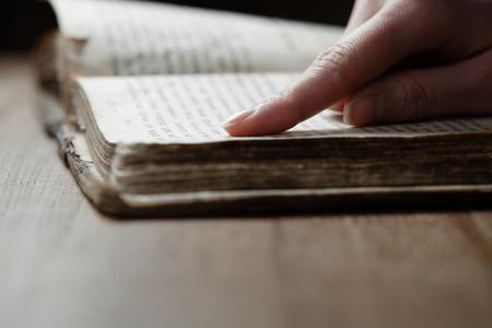 木製のテーブルと聖書を読んで暗いロムで古い聖書本の女性の指を押した