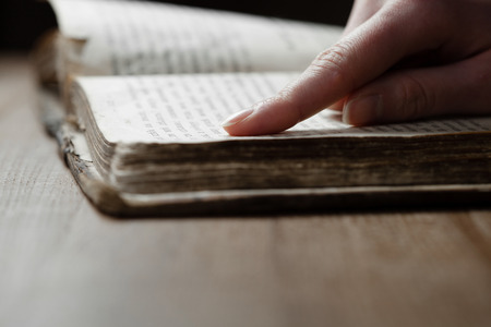 woman finger presses on old bible book in a dark romm over wooden table and reading a bible