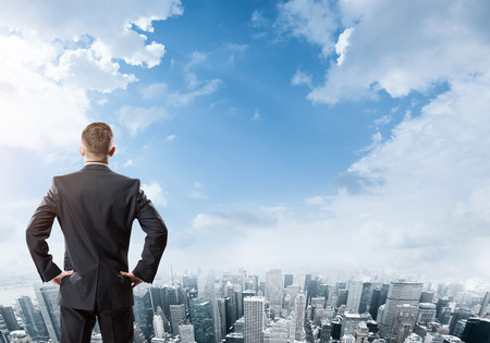 Businessman standing and looking at the city Stock Photo