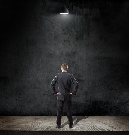 liderazgo empresarial: el hombre busca en la pizarra en el interior con la lámpara Bombilla en fondo de la pizarra con espacio de copia Foto de archivo