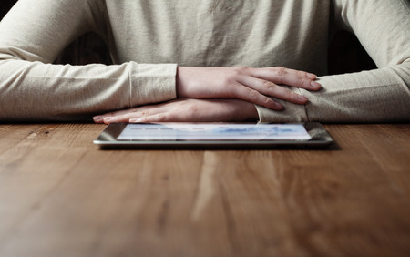 blank screen: woman looking at  screen digital tablet over wooden table