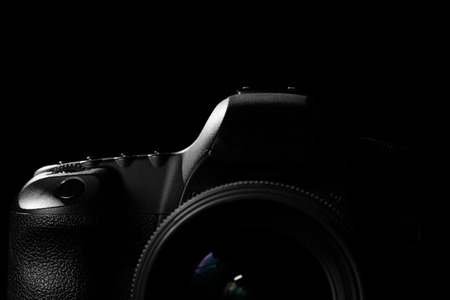 photojournalism: Image of a professional modern DSLR camera low key image  Modern DSLR camera with a very wide aperture lens on in a dark space. Top part of a camera is visible and the rest goes into the shadow Stock Photo