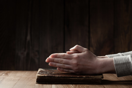 manos orando: Manos femeninas que ruegan en la biblia Foto de archivo