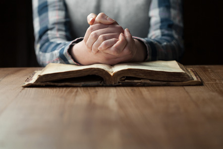 religions: Woman hands praying with a bible in a dark over wooden table
