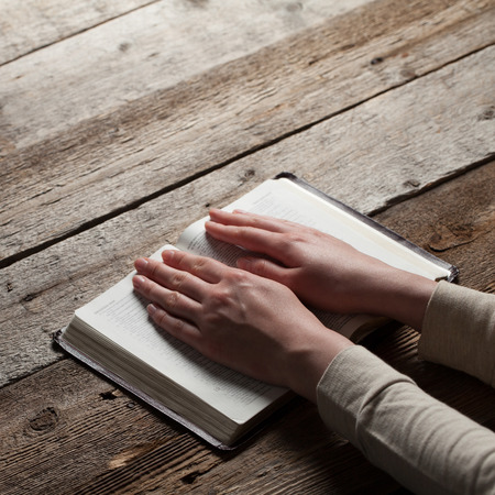 reverent: Woman hands praying with a bible in a dark over wooden table