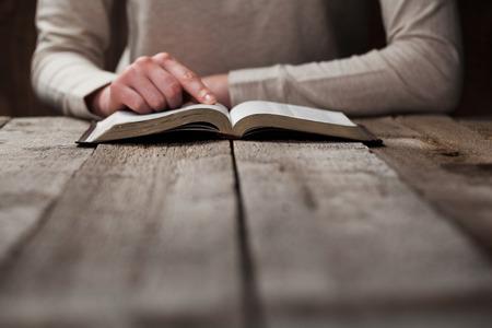 女性は、聖書を手します。彼女、読み取りおよび木製のテーブルの上暗い空間では、聖書を祈る 写真素材
