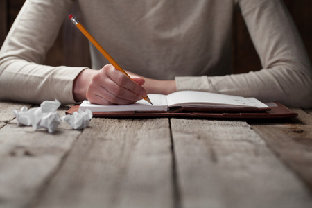 write letter: hand writes with a pen in a notebook