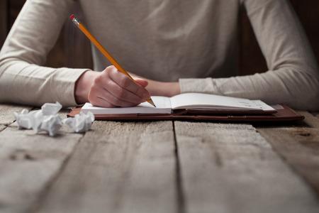 mão escreve com uma caneta em um caderno