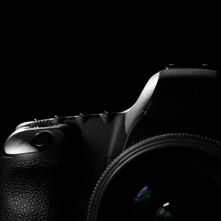 Image of a professional modern DSLR camera low key image  Modern DSLR camera with a very wide aperture lens on in a dark space. Top part of a camera is visible and the rest goes into the shadow Stock Photo