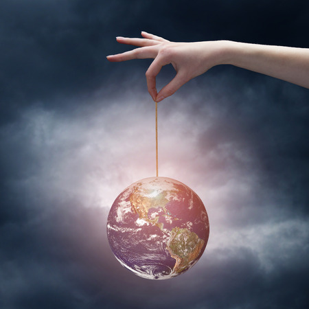 obsolescence: human hand holding Earth planet on rope.
