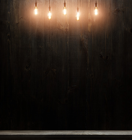 switched: wooden interior room with classic Edison light bulb on wooden background switched on. retro edison light bulb