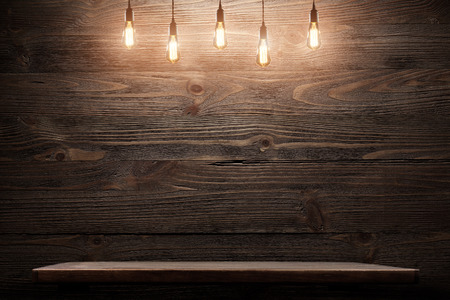 Wood shelf grunge industrial interior with edison light bulb
