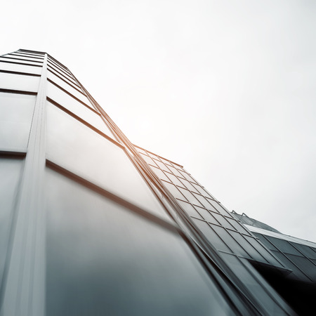 real estate growth: Wide angle abstract background view of steel light blue high rise commercial building skyscraper made of glass exterior. concept of successful industrial architecture and office center building Stock Photo