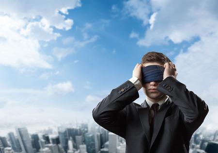 ojos vendados: El hombre de negocios de pie con los ojos vendados con la ciudad en el fondo