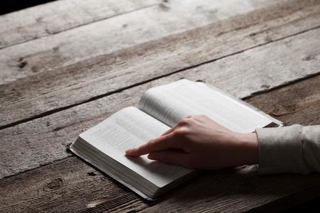 leer biblia: Mujer dedo presiona en el libro de la biblia sobre fondo de madera