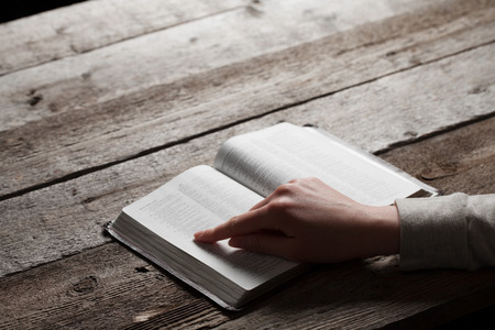 bible background: woman finger presses on bible book over wooden background