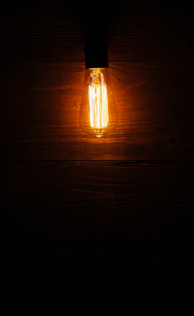 switched: A classic Edison light bulb on wooden background switched on. retro edison light bulb