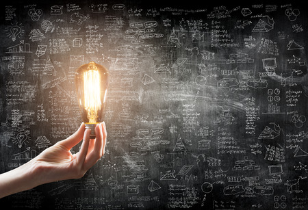 power icon: hand holding Light bulb on blackboard background
