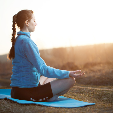 yoga outside: Brunette woman practicing yoga outside during sunset wearing sports wear with eyes closed Stock Photo