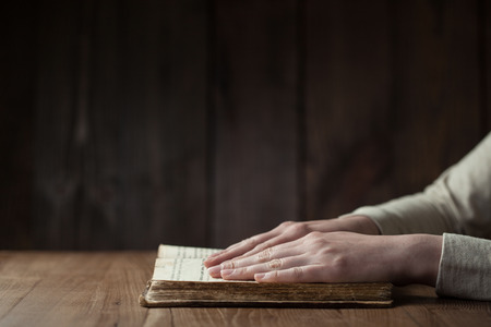 praying hands: Woman hands praying with a bible Stock Photo