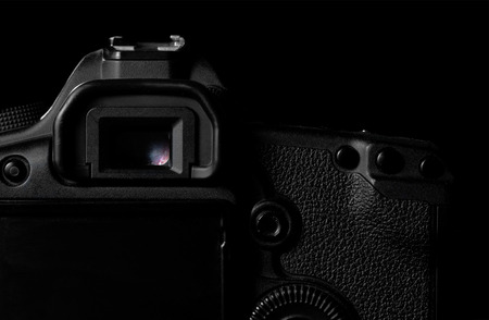 photojournalism: Image of a professional modern DSLR camera low key image  Modern DSLR camera  in a dark space. Top part of a camera is visible and the rest goes into the shadow