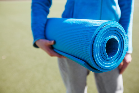 A woman walking with a yoga mat Stock Photo
